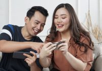 man and woman sitting on sofa and playing on mobile phone