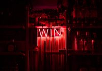 """red and white neon light """"win"""" signage"""
